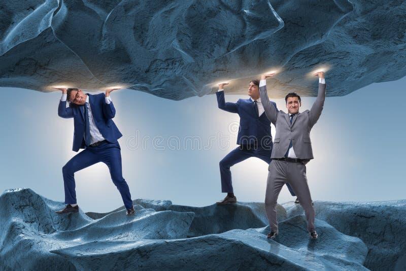 Камень бизнесмена поддерживая под давлением стоковое фото rf