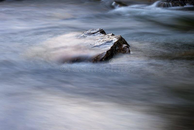Камень в реке с быстроподвижной водой вокруг стоковые изображения rf