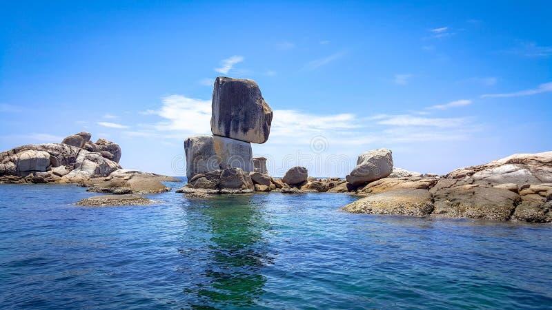 Камень штабелированный в море с голубым небом и дневним светом стоковые изображения