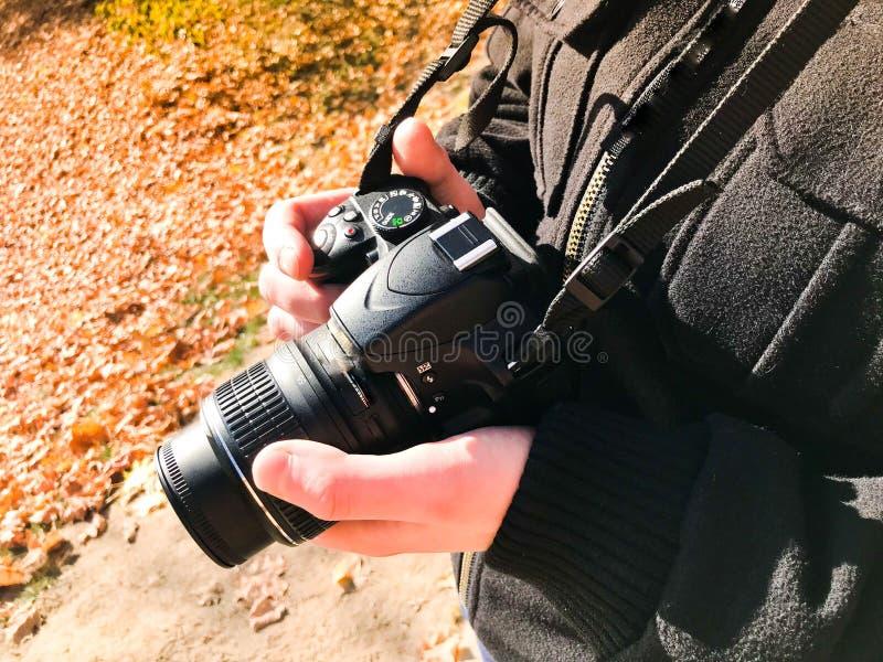 Камера большого черного современного цифрового зеркала профессиональная в руках фотографа Фотограф человека регулирует камеру стоковое изображение