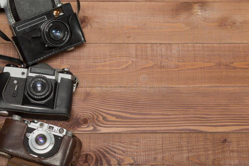 Камера 3 годов сбора винограда в их случаи на деревянной предпосылке стоковые изображения