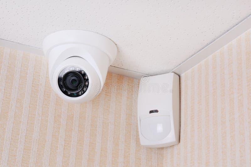 Камера слежения и детектор движения установленный на потолок в комнату стоковые фото