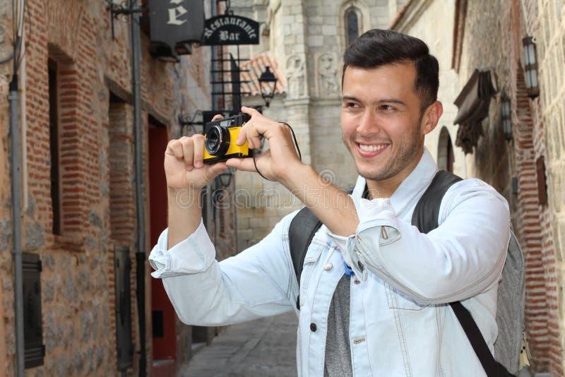 Камера удерживания молодого человека во время каникул в Европе стоковое фото