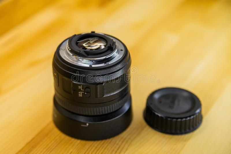 Камера фото DSLR или видео- конец-вверх объектива на деревянной предпосылке, задаче, концепции работы человека камеры фотографа,  стоковые изображения