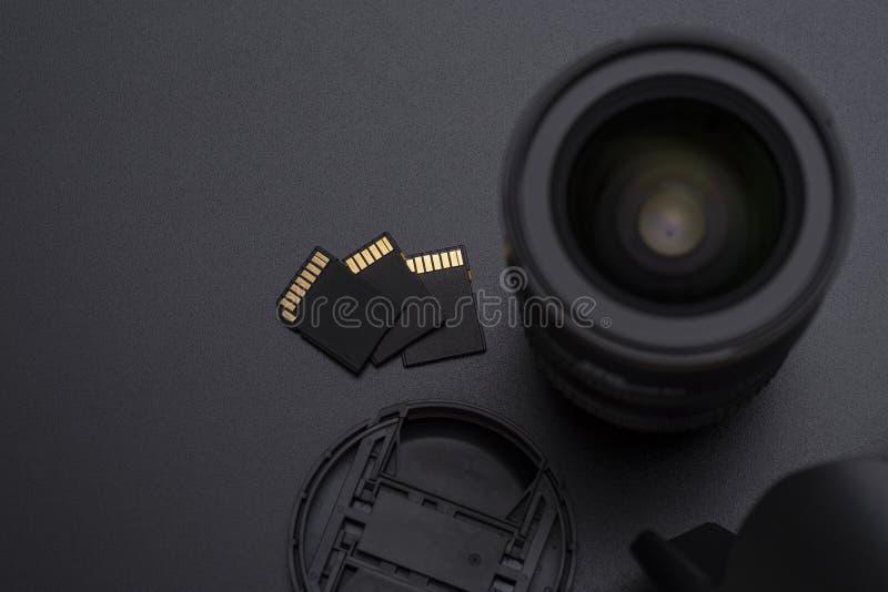 Камера фото DSLR или объектив видео, карты памяти SD, клобук и передний конец-вверх крышки отображают стоковое фото rf