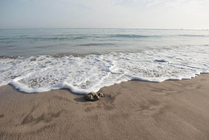 Камешек волны причаливая на песке пляжа стоковые фото