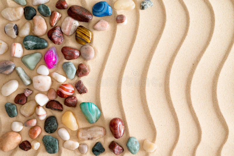 Камешки и драгоценные камни на золотом песке пляжа стоковые изображения