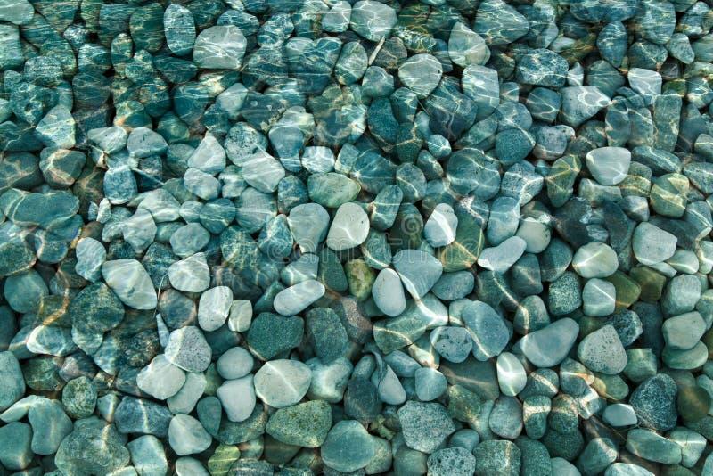 Камешки и утесы под предпосылкой воды стоковые изображения rf