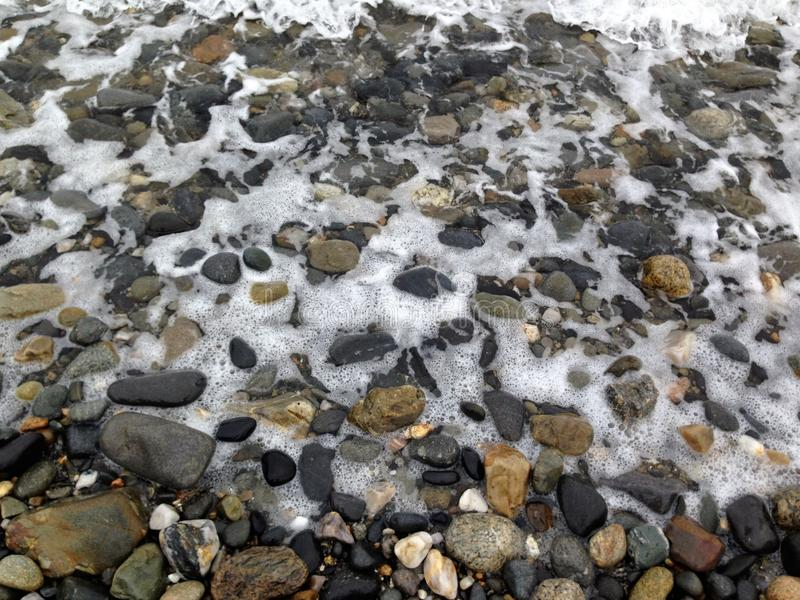 Камешки на пляже с волнами стоковые фотографии rf