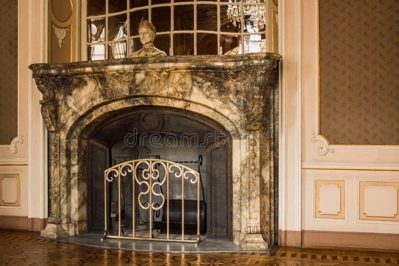 Камин серого гранита каменный в роскошной комнате богатого особняка интерьер залы стиль барокко стоковые фото