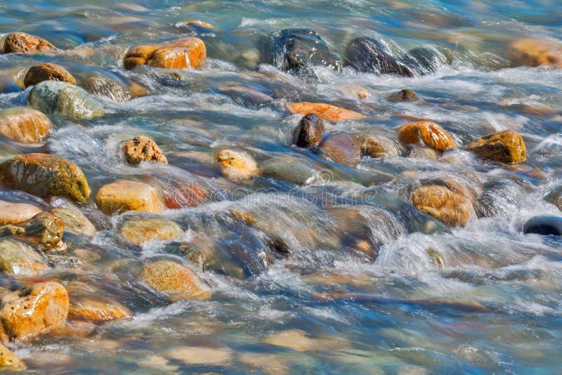 Камни камешка в конце речной воды вверх по взгляду стоковые фотографии rf