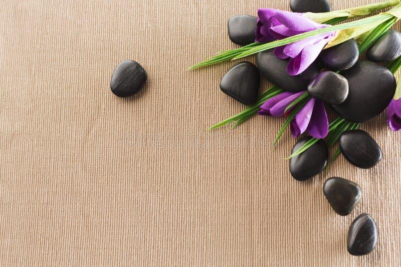 Камни массажа с цветками на циновке стоковые фотографии rf