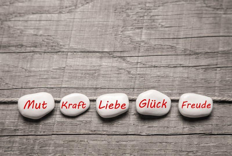 Камни с немецкими словами для влюбленности на деревянной предпосылке. стоковое изображение