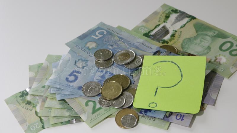 Канадское распространение денег на таблице с липким примечанием с вопросительным знаком концепция финансовой запутанности и не зн стоковые фотографии rf
