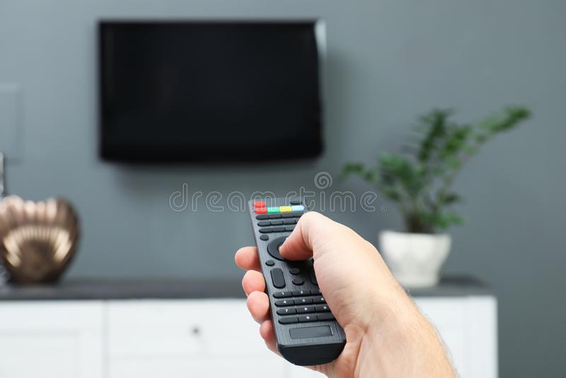 Каналы человека переключая на плазменный телевизор стоковое фото rf