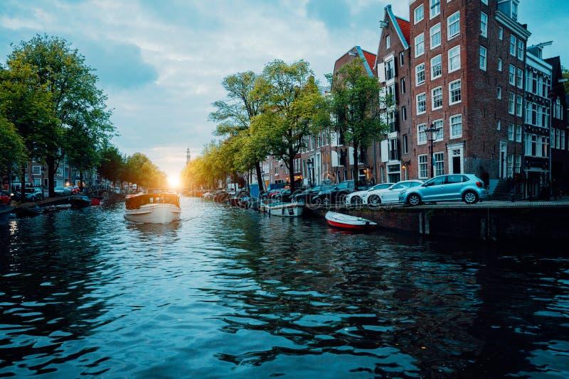 Канал Амстердама красивый дерев-выровнянный со шлюпкой круиза в теплом свете захода солнца стоковое изображение