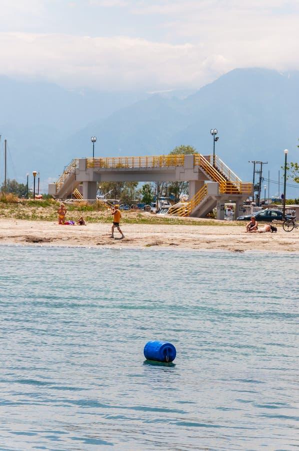 Канал пешеходного моста надводный, туристы отдыхая на пляже Эгейского моря, Mount Olympus на предпосылке стоковое фото