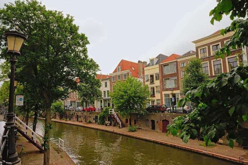 канал ` oudegracht ` в Utrecht, с типичными голландскими домами, при погреба приходя вне на старый причал стоковое изображение