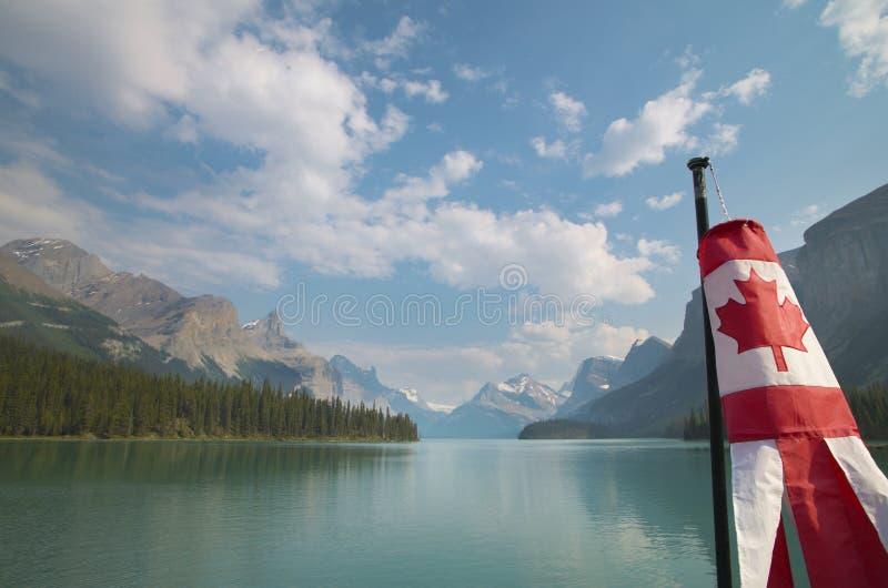 Канадский ландшафт с горами, озером Maligne и флагом альбеда стоковые изображения rf