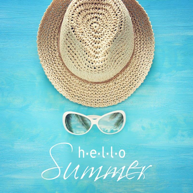 Каникулы и лето отображают с шляпой и солнечными очками пляжа fedora над голубой деревянной предпосылкой стоковые фотографии rf