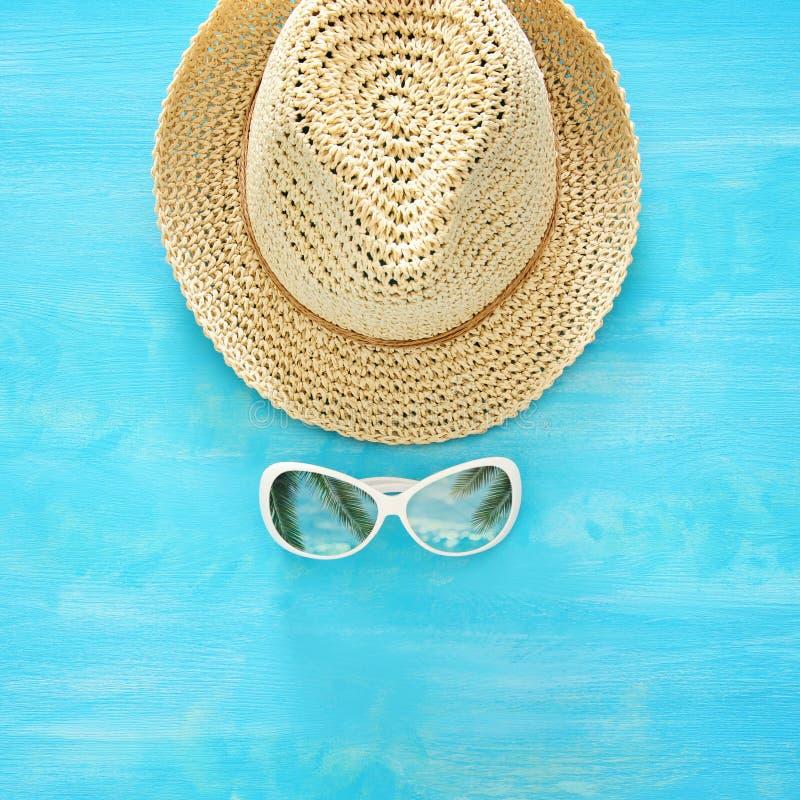 Каникулы и лето отображают с шляпой и солнечными очками пляжа fedora над голубой деревянной предпосылкой стоковое изображение