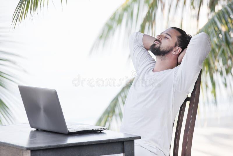 Каникулы и технология Работа и перемещение Молодой бородатый человек используя ноутбук пока сидящ на баре кафа пляжа стоковые изображения rf