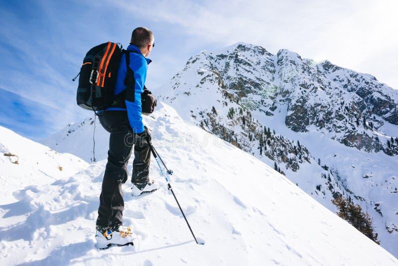 Каникулы зимы: альпинист принимает остатки смотря mountai стоковые фото