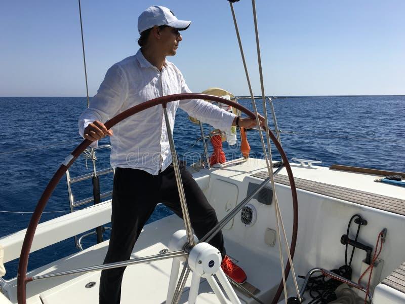 Каникулы рулевого колеса яхты плавания молодого человека стоковая фотография rf