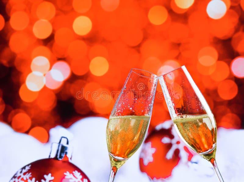 Каннелюры Шампани с золотыми пузырями на красных bokeh светов рождества и предпосылке украшения шариков стоковое фото rf