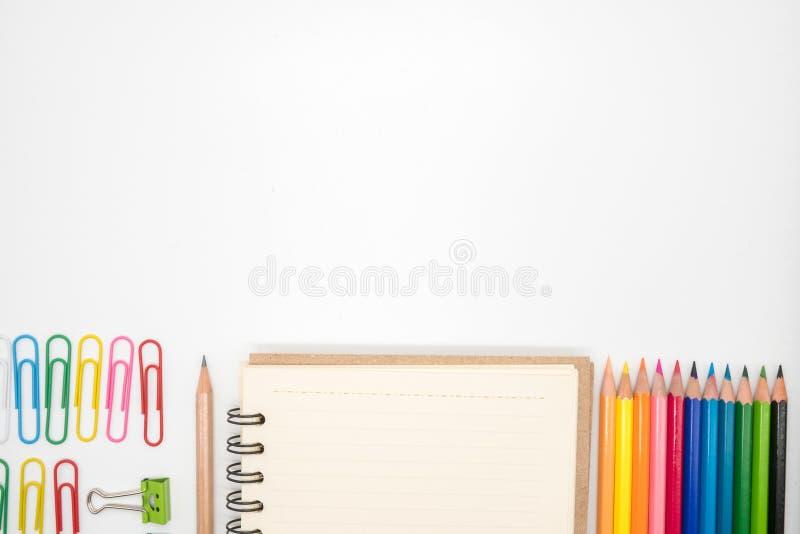 Канцелярские принадлежности включили бумажные зажимы, карандаш, тетрадь и карандаши цвета на белой предпосылке стоковое фото