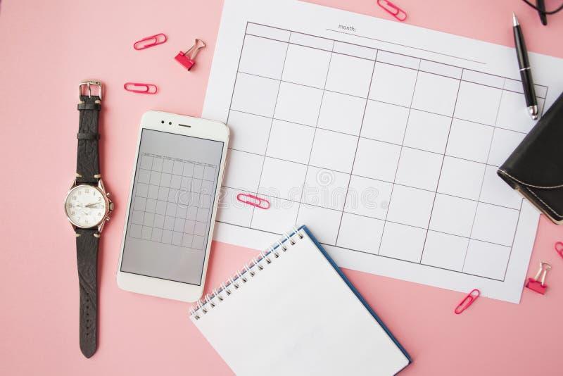 Канцелярские принадлежности, натюрморт с календарем и аксессуарами, пустая тетрадь, часы и смартфон стоковые фото
