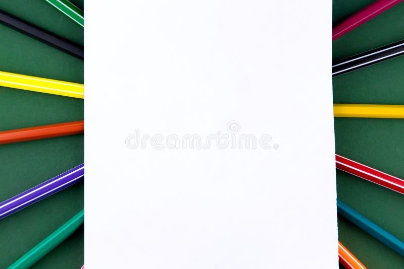 Канцелярские принадлежности поставок школьного офиса на зеленом столе предпосылки с белой бумагой над космосом экземпляра r стоковые фотографии rf