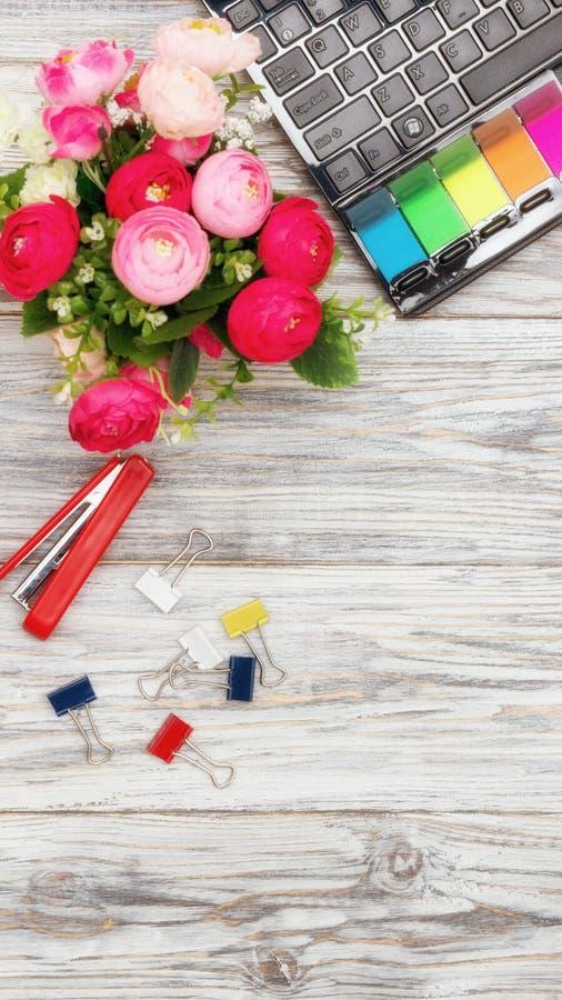 Канцелярские принадлежности, цветки и компьтер-книжка стоковое фото