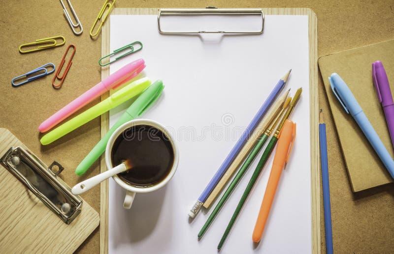 Канцелярские принадлежности: доска сзажимом для бумаги, зажимы, карандаши, ручки цвета, paintbrush, стоковые фотографии rf
