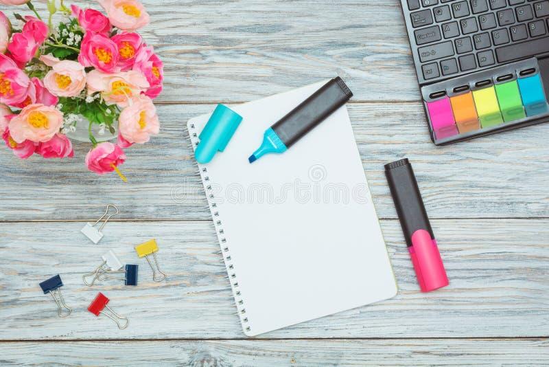Канцелярские принадлежности, цветки и блокнот стоковые изображения