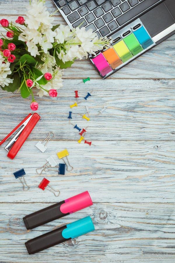 Канцелярские принадлежности, цветки и компьтер-книжка стоковая фотография