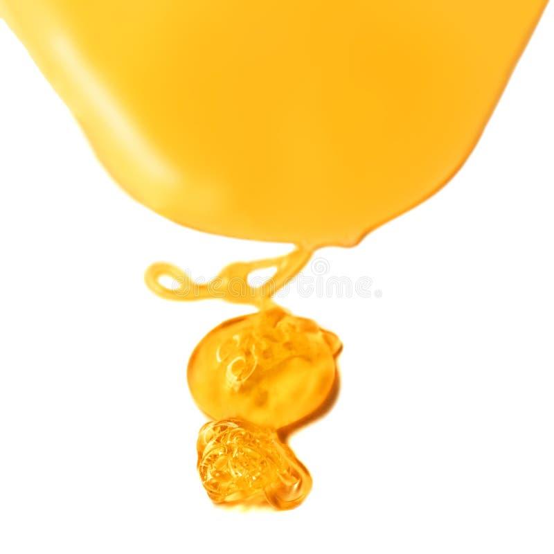 Капание меда от деревянного ковша меда над желтой предпосылкой стоковое изображение rf