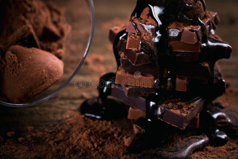 Капание сиропа шоколада на стоге темноты и стога молочного шоколада, трюфелей стоковая фотография rf