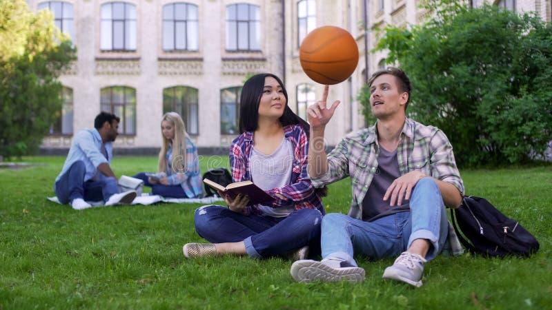 Капитан баскетбольной команды flirting с красивым biracial отношением студента стоковые фото