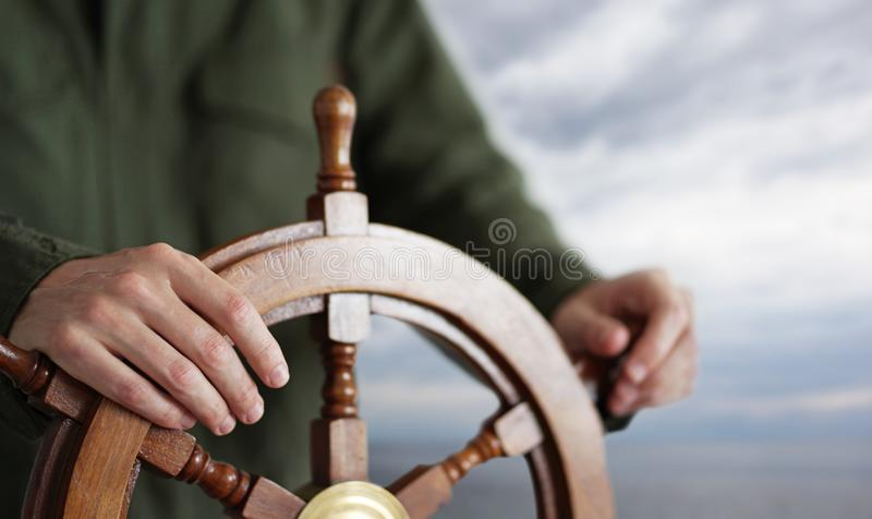 Капитан держа руку на штурвале корабля стоковое изображение rf