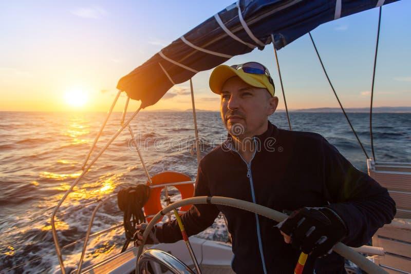 Капитан управляет яхтой плавания на море во время захода солнца Спорт стоковые изображения