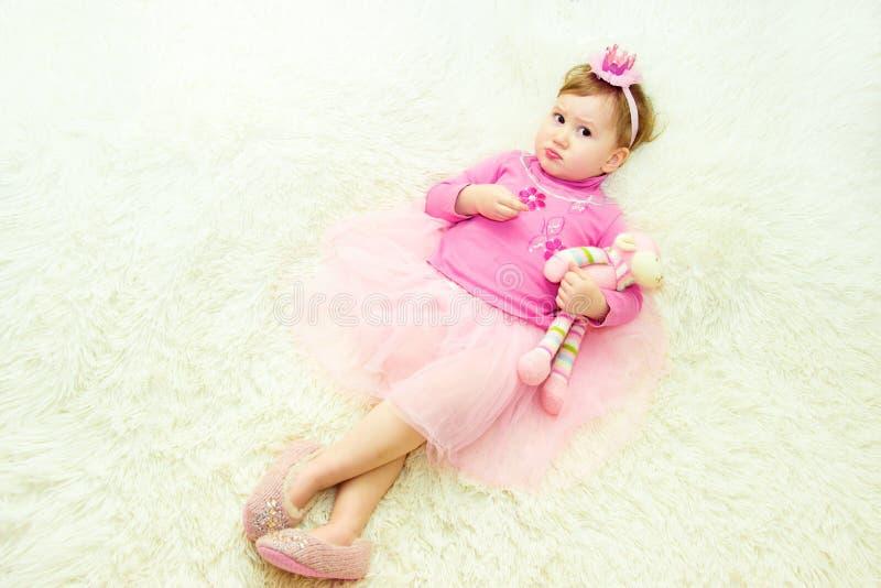 Капризная маленькая девочка лежит на кровати с игрушкой в ее руках стоковые изображения