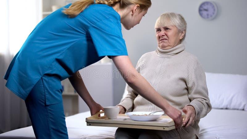 Капризная старшая дама отказывая опостылеть обедающий диеты в медицинском центре, заботе стоковое фото rf