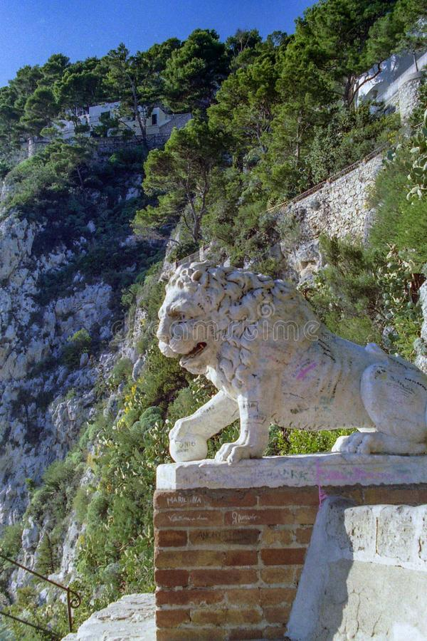 КАПРИ, ИТАЛИЯ, 1967 - мраморный лев наблюдает над парком садов Augustus в Капри стоковые изображения rf