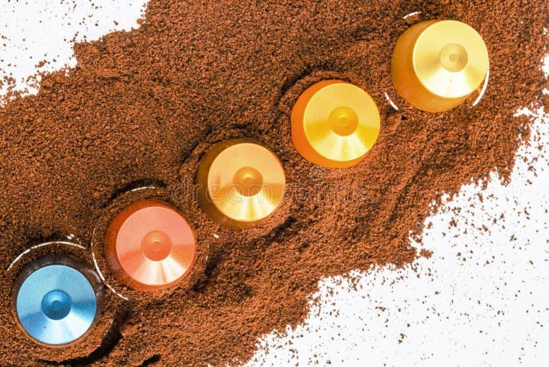 Капсулы кофе помещенные на кровати порошка кофе стоковое фото