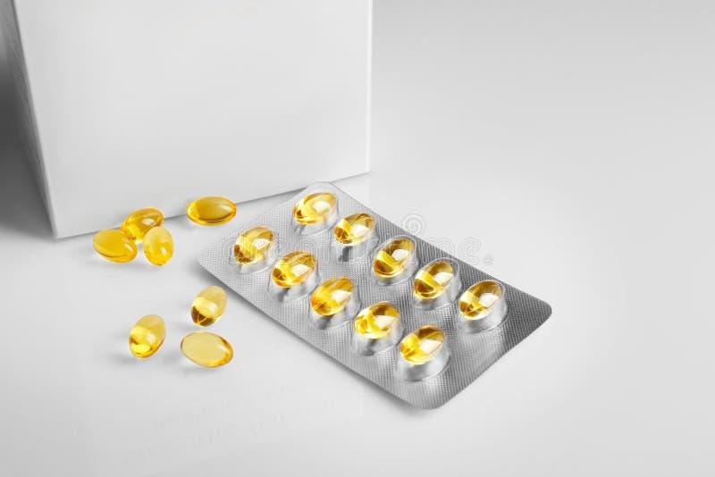 Капсулы масла печени трески на белой предпосылке стоковое изображение