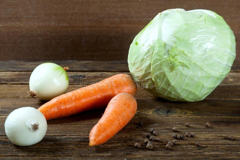 Капусты моркови и лука на деревянном столе royalty free stock photos