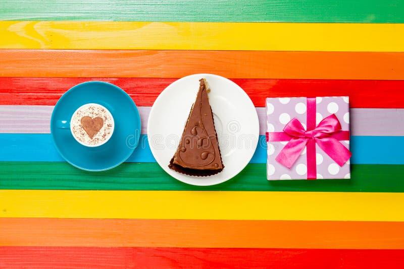 Капучино чашки кофе с тортом и подарочной коробкой стоковые изображения
