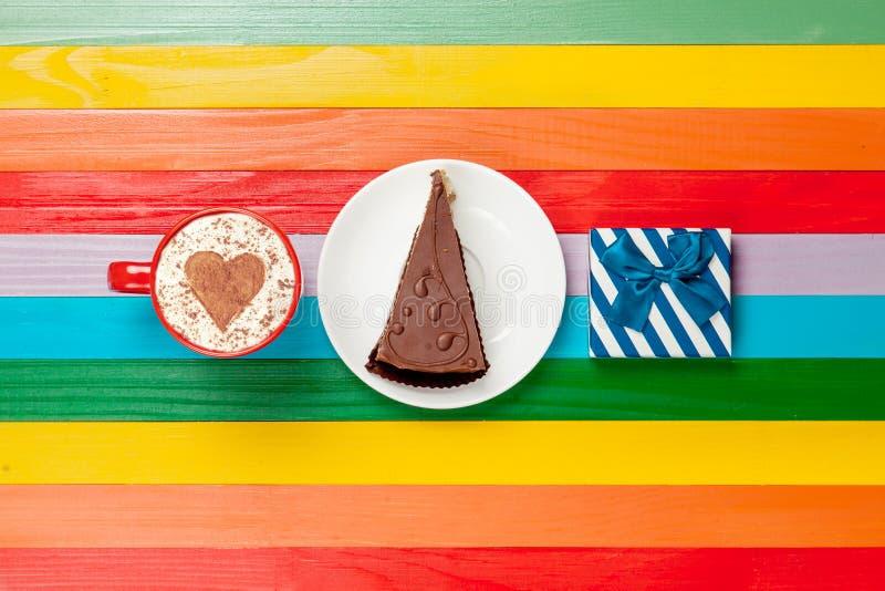 Капучино чашки кофе с тортом и подарочной коробкой стоковое изображение