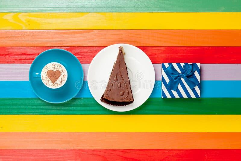 Капучино чашки кофе с тортом и подарочной коробкой стоковое фото rf